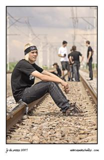 JP Du Preez sitting on a railway line with the revolution and kfd skateboarding teams in the back ground on the way to klerksdorp photographed by Marcus Maschwitz