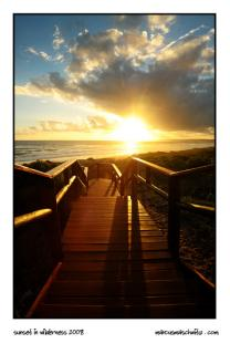 the sun setting in wilderness standing on a walkway to the beach photographed by marcus maschwitz