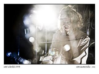 Portrait of a mad scientist in a lab behind broken glass photographed by marcus maschwitz