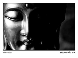 A silver statue of buddha photographed by Marcus Maschwitz