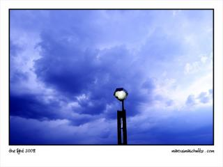 A street light with clouds behind photographed by marcus maschwitz