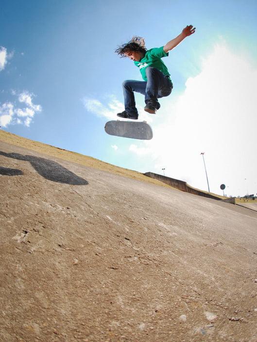 Adam Woolf kickflips on a drain bank in Johannesburg
