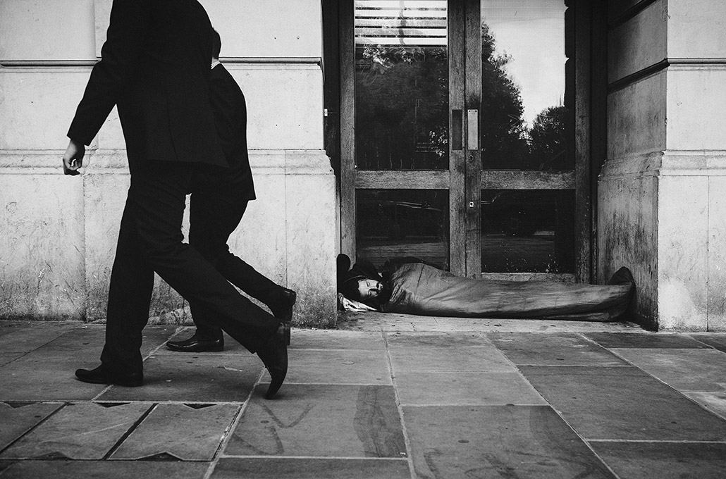 Business men walking passed a homeless person in London photographed by Marcus Maschwitz