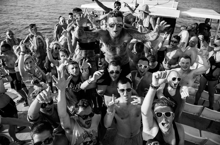 Matthew Pritchard of Dirty Sanchez crowdsurfing on a boat in the ocean photographed by Marcus Maschwitz