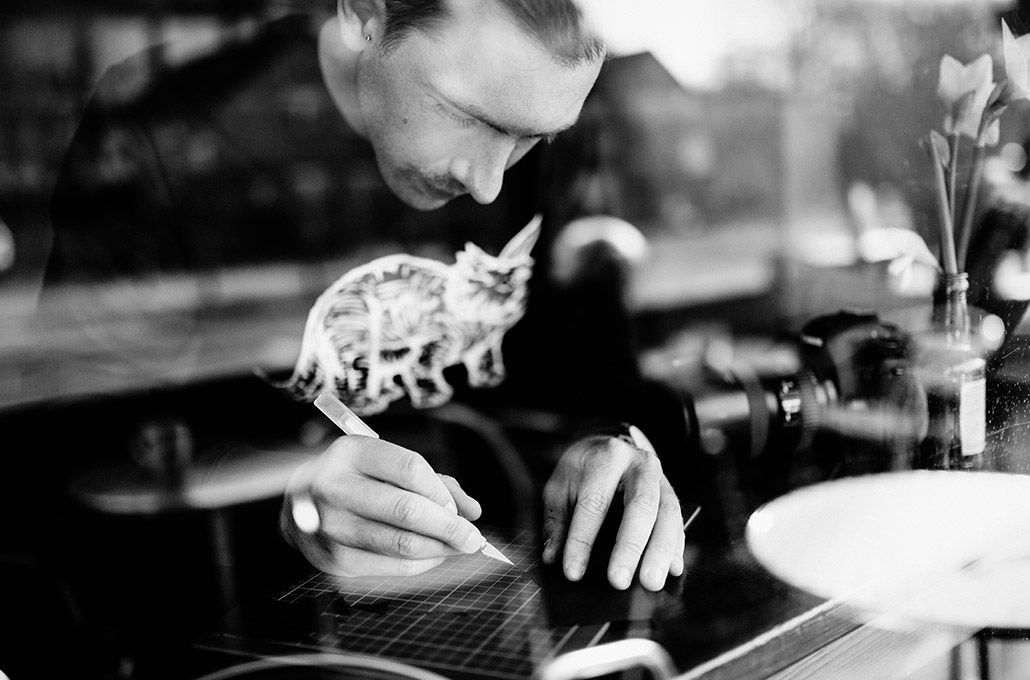 Paperboyo cutting art in a coffee shop photographed by Marcus Maschwitz