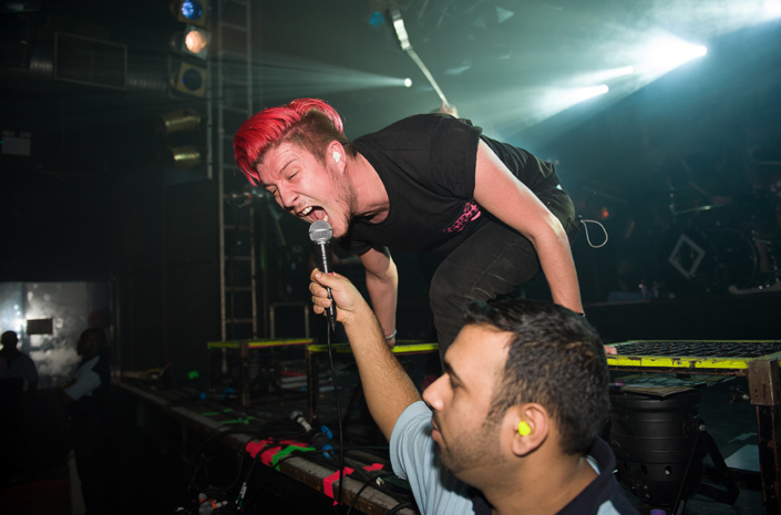 Sean Smith of The Blackout singing into a mic held by a security guard photographed by Marcus Maschwitz