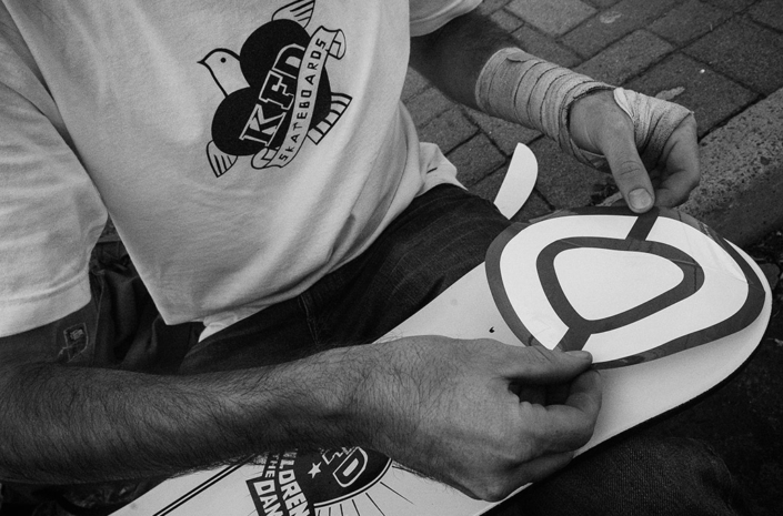 Applying stickers on a skateboard photographed by Marcus Maschwitz