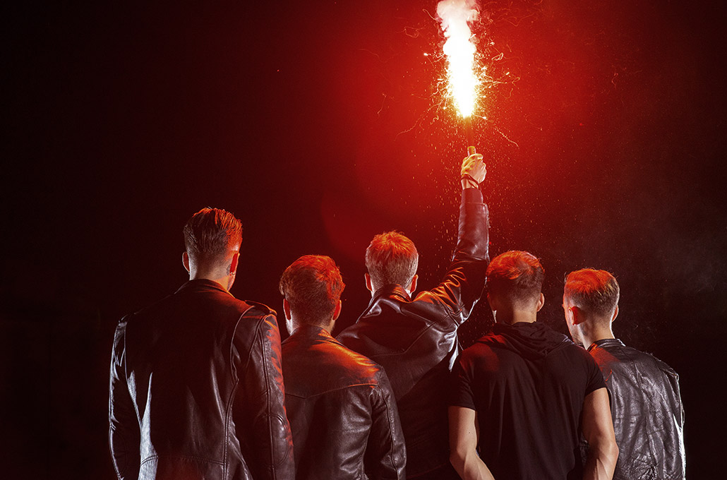 Young Guns with a red flare on a rooftop in London photographed by Marcus Maschwitz